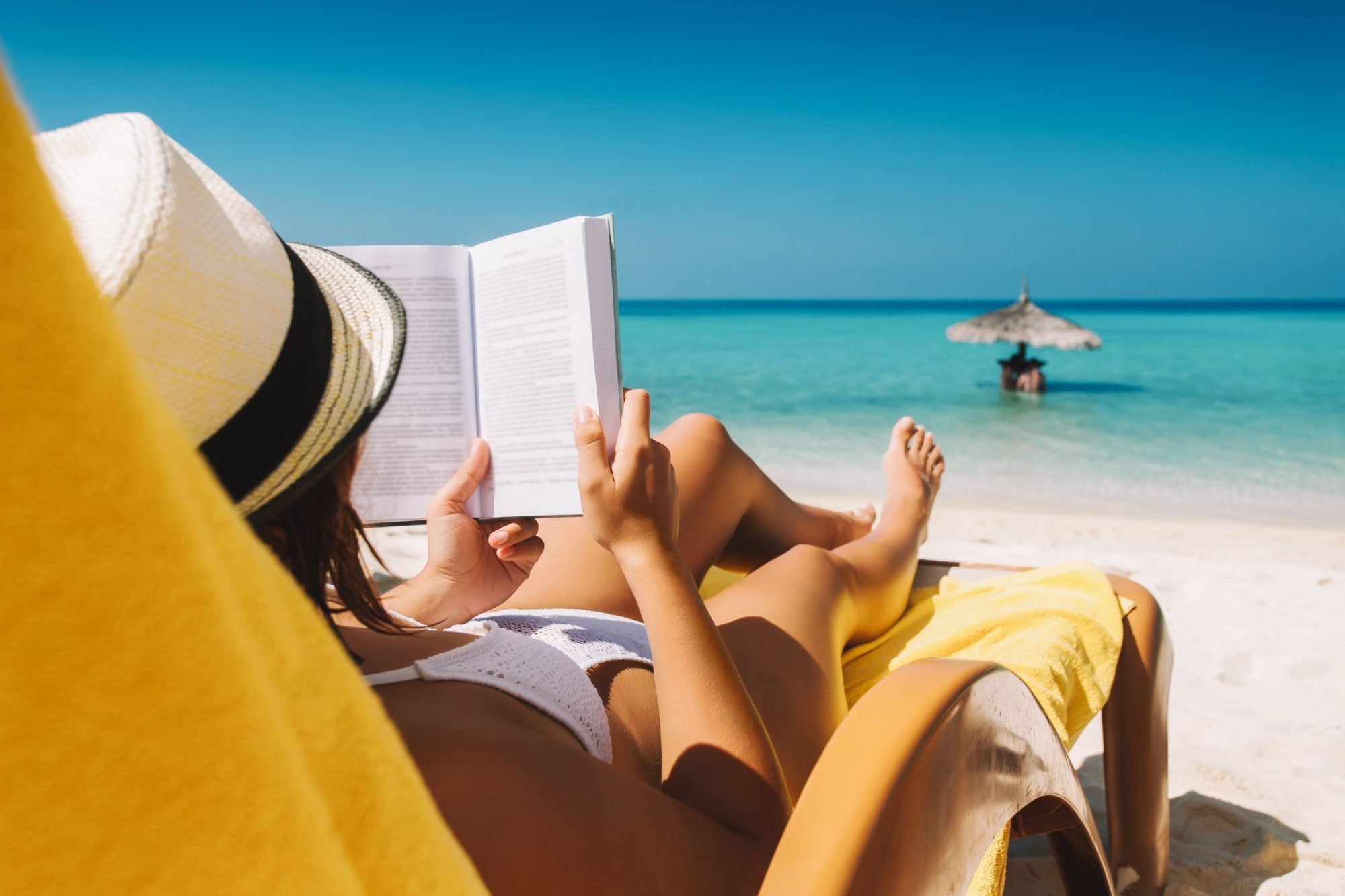 Woman on sunbed reading book under parasol at tropical island